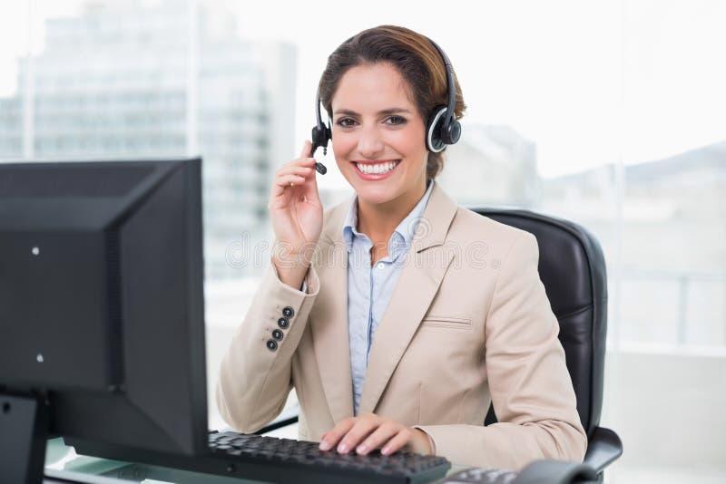 拿着耳机的微笑的女实业家 免版税库存图片