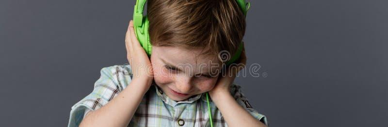 拿着耳机的愉快的被聚焦的幼儿听到音乐 免版税库存图片