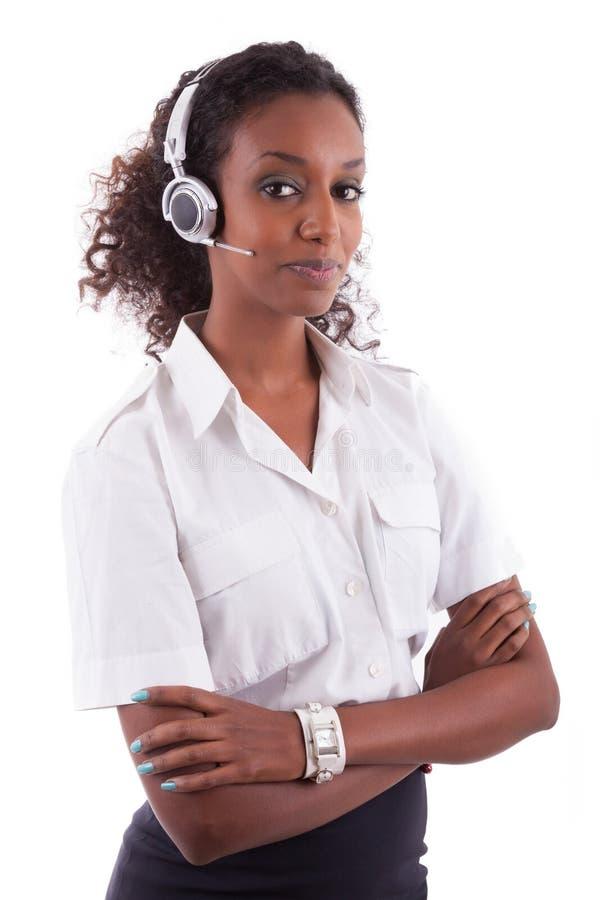 拿着耳机-黑人的非裔美国人的帮助台工作者 库存照片