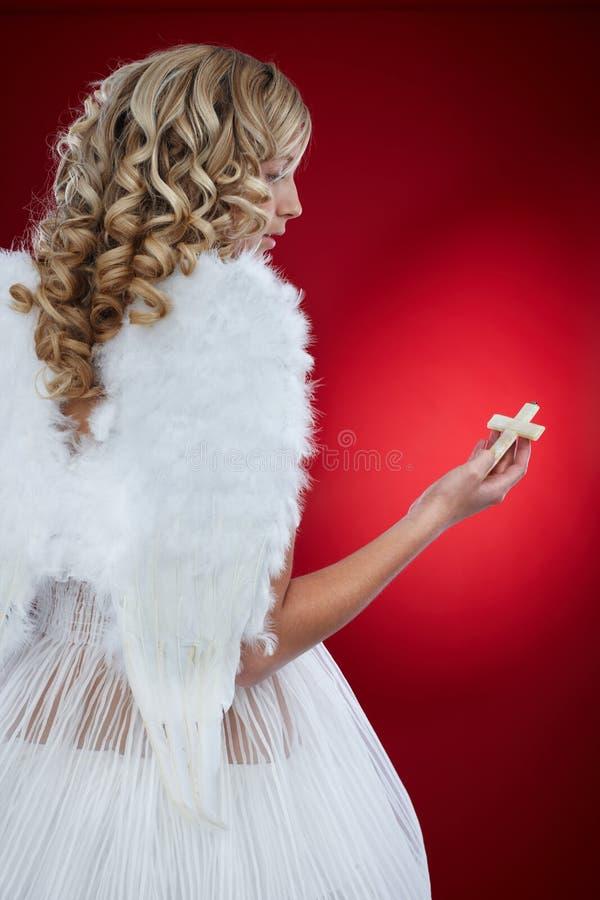 拿着耶稣受难象的天使 库存图片
