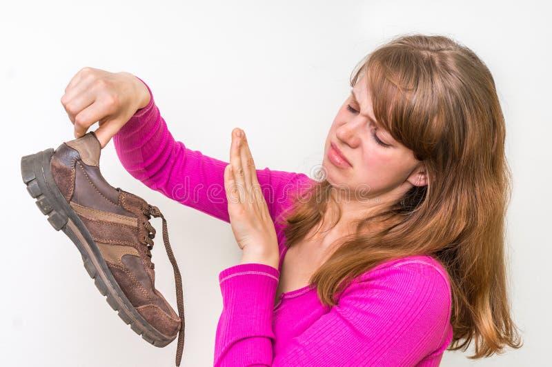 拿着肮脏的腐败的鞋子的妇女 免版税图库摄影