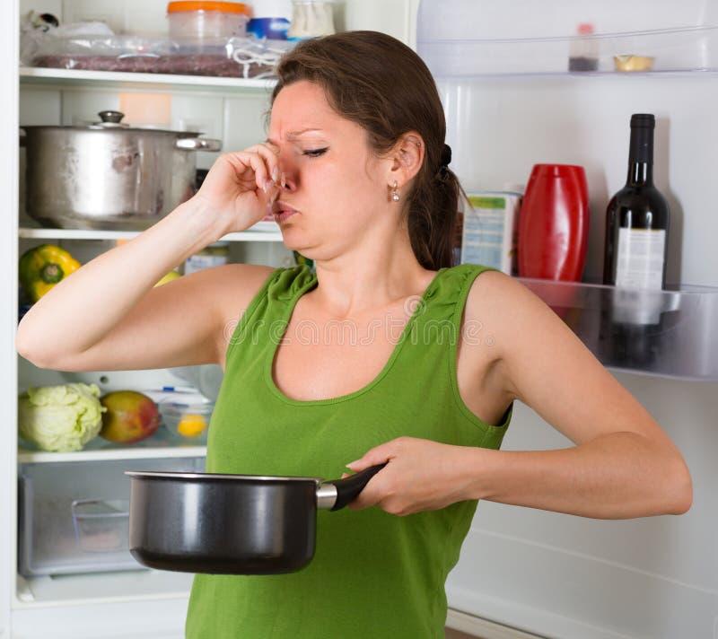 拿着肮脏的食物的妇女在frige附近 图库摄影