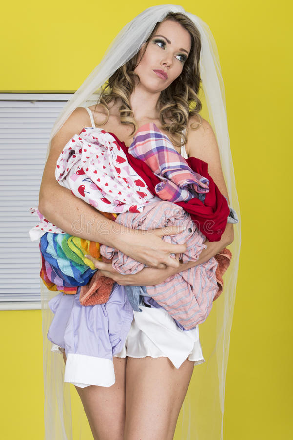 拿着肮脏的洗衣店的婚礼面纱的可爱的无印记的少妇不快乐 库存照片