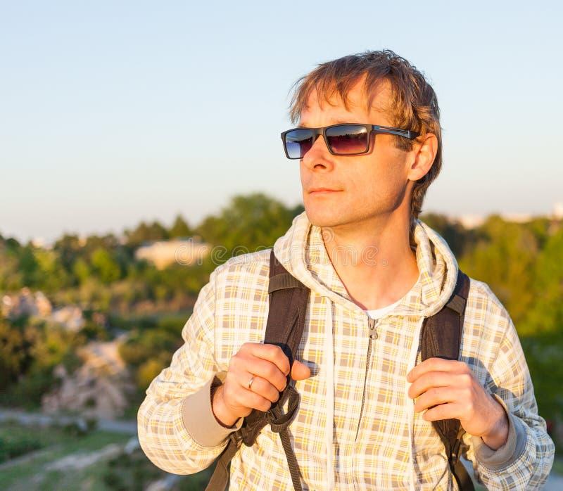 拿着背包和看日落的愉快的人远足者 免版税库存照片