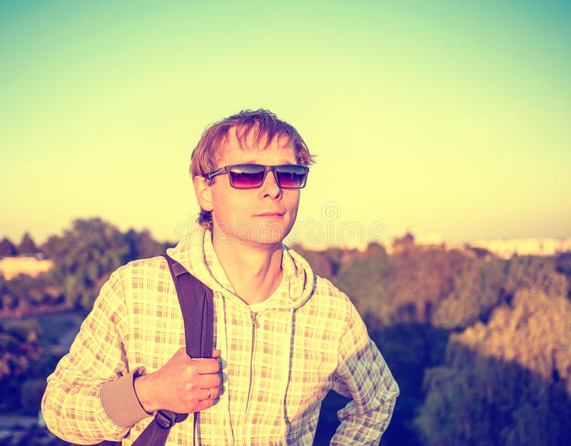 拿着背包和看日落的风格化colorized葡萄酒愉快的人画象 免版税库存图片