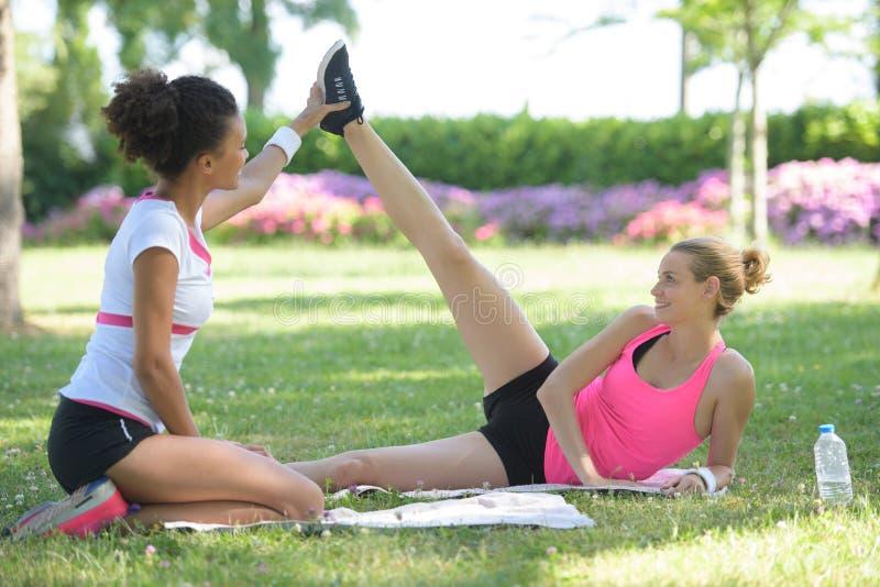 拿着腿妇女的个人教练员舒展在公园 图库摄影