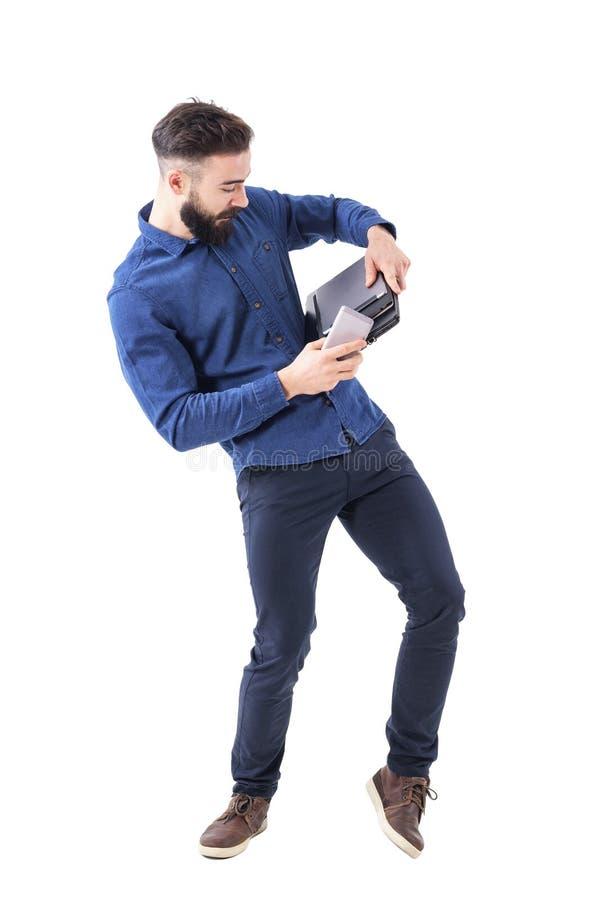 拿着膝上型计算机、片剂和手机从跌倒的笨拙的年轻有胡子的商人 免版税库存照片