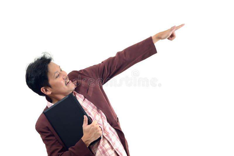 拿着膝上型计算机和指向和看对他的sid的商人 库存照片