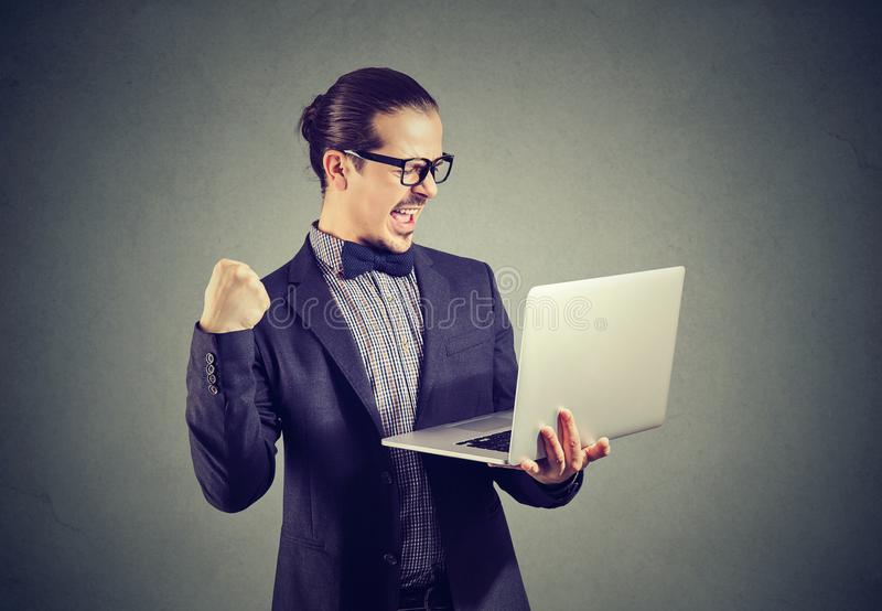 拿着膝上型计算机和看起来愉快赢取的激动的商人 图库摄影