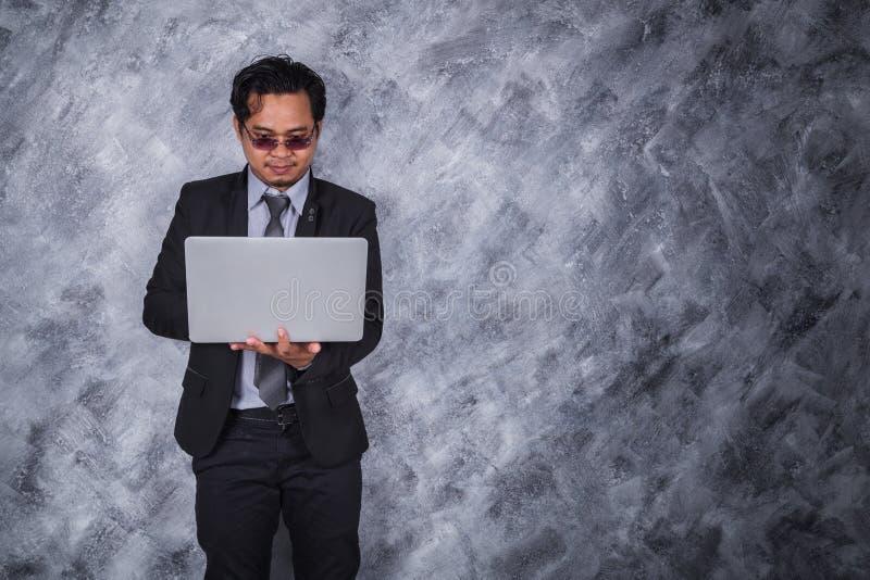 拿着膝上型计算机有墙壁背景的商人 免版税库存照片