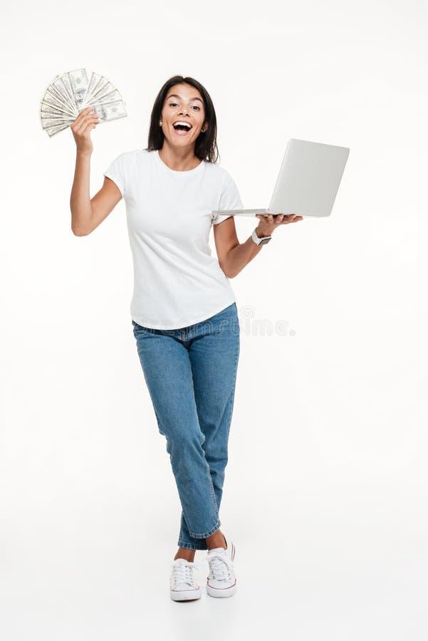 拿着膝上型计算机的一名激动的快乐的妇女的全长画象 库存图片