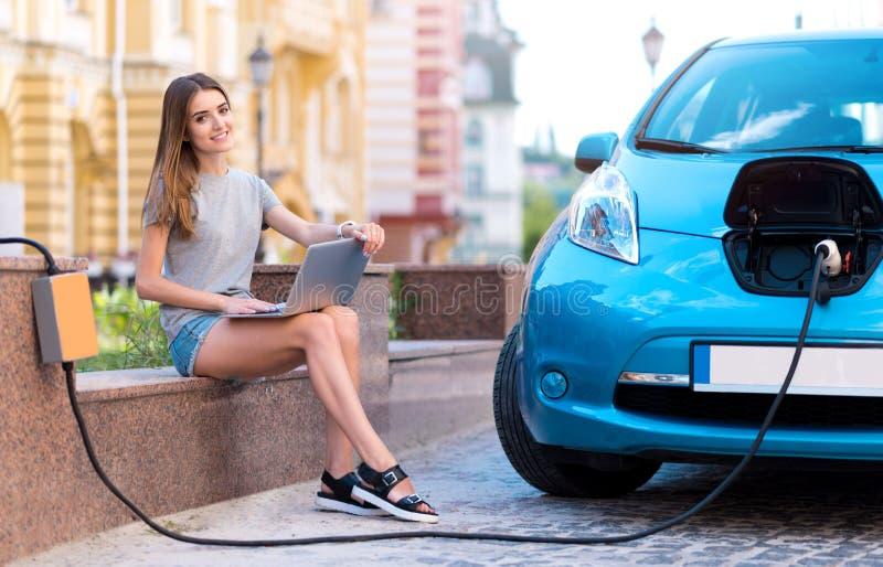 拿着膝上型计算机的妇女,当充电汽车时 免版税库存照片