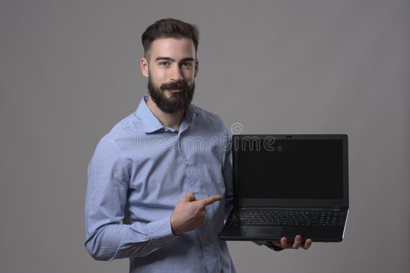 拿着膝上型计算机的微笑的愉快的年轻成人商人喜怒无常的画象和指向和空白的屏幕 免版税库存图片