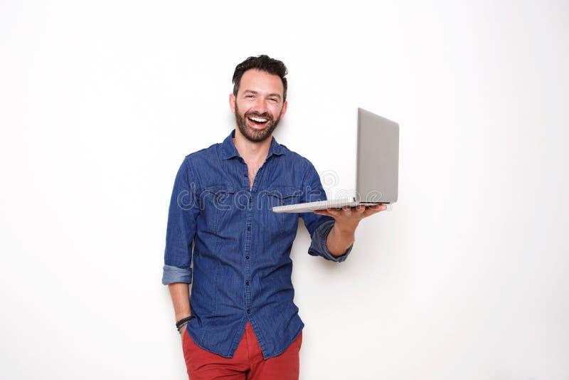 拿着膝上型计算机的微笑的成熟人 库存照片