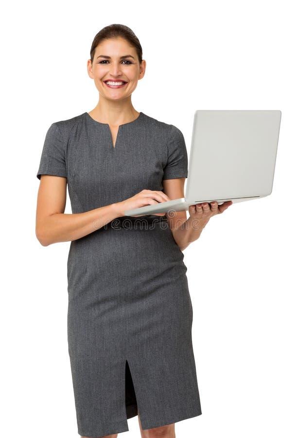 拿着膝上型计算机的愉快的中间成人女实业家 库存照片
