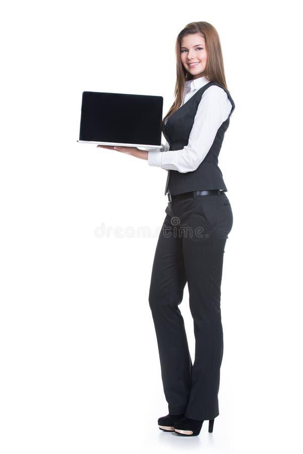 拿着膝上型计算机的成功的年轻女商人。 免版税图库摄影