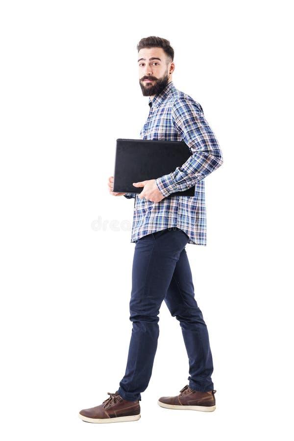 拿着膝上型计算机的时髦的现代有胡子的商人在胳膊走下 侧视图 库存照片