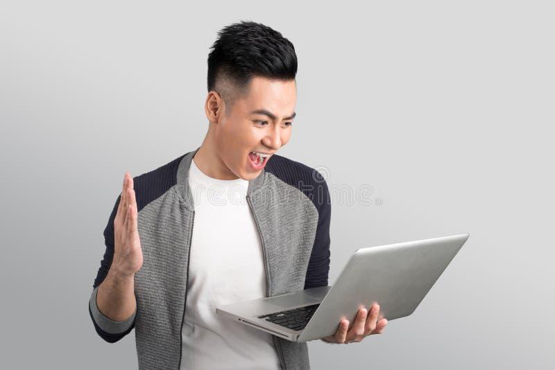 拿着膝上型计算机的确信的年轻亚洲商人 库存图片