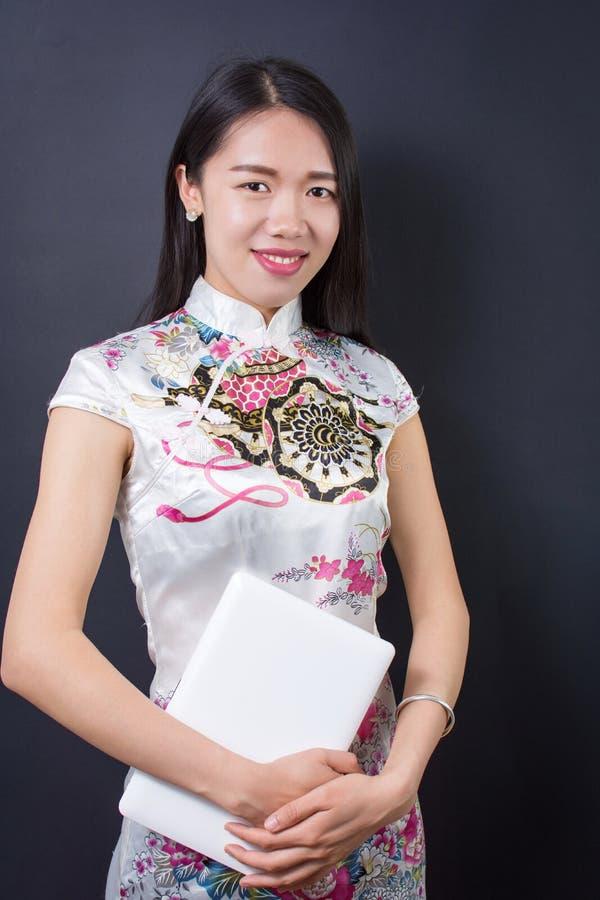拿着膝上型计算机设备的年轻亚裔妇女 免版税库存照片