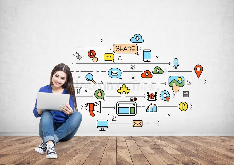 拿着膝上型计算机,社会媒介的牛仔裤的十几岁的女孩 免版税库存图片