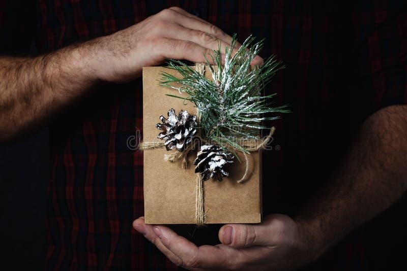 拿着自创圣诞礼物黑暗的背景圣诞节背景的男性手 免版税库存照片