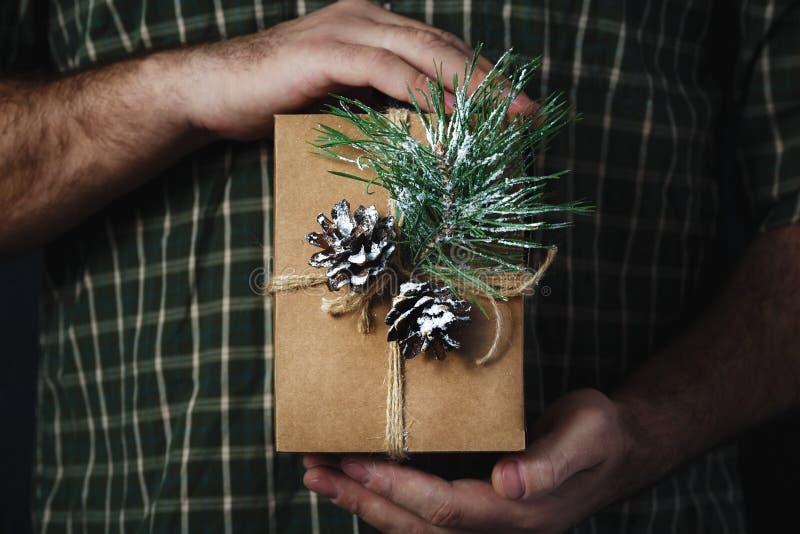 拿着自创圣诞礼物黑暗背景的圣诞节背景男性手 免版税图库摄影