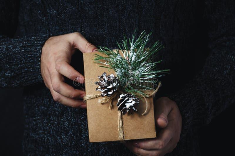 拿着自创圣诞礼物黑暗背景的圣诞节背景男性手 图库摄影