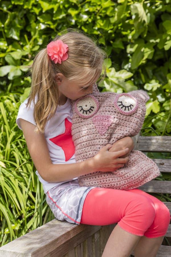 拿着自创玩具钩针编织猫头鹰的女孩在庭院里 库存图片