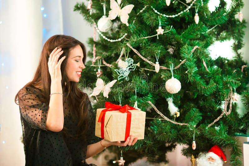拿着自圣诞前夕的愉快的少妇圣诞节礼物箱子 库存照片