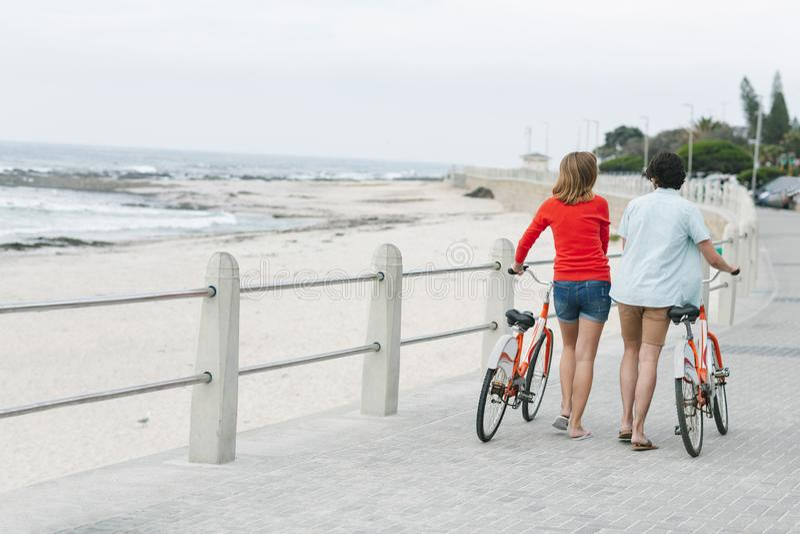 拿着自行车的白种人夫妇,当走在路面在散步附近时 库存图片
