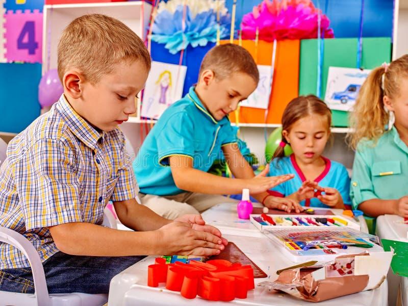 拿着色纸和胶浆在桌上的孩子  免版税图库摄影