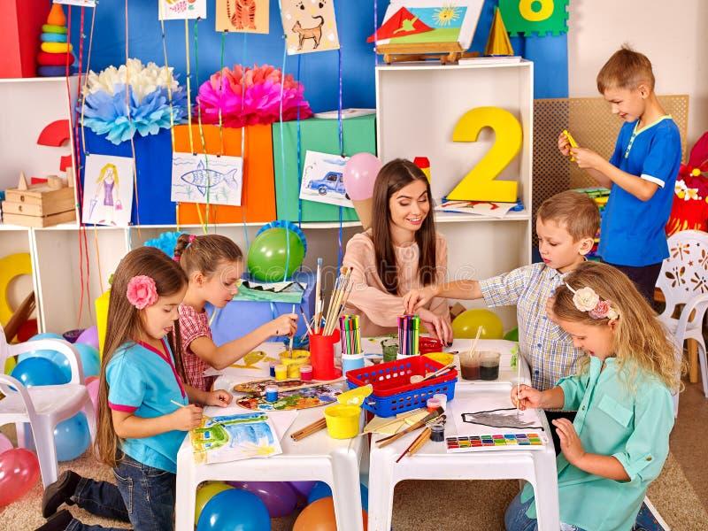 拿着色纸和胶浆在桌上的孩子  免版税库存照片