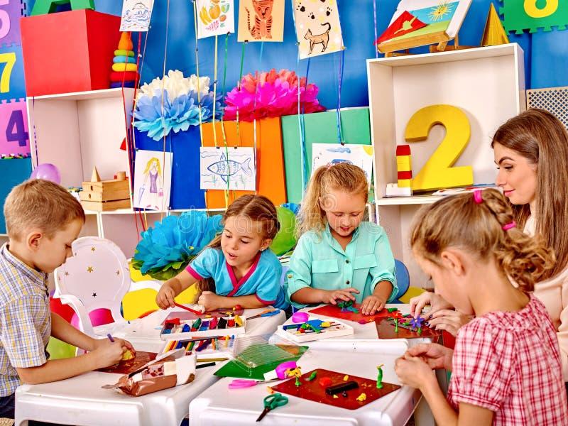 拿着色纸和胶浆在桌上的孩子  库存照片