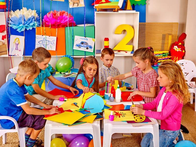 拿着色纸和胶浆在桌上的孩子  库存图片