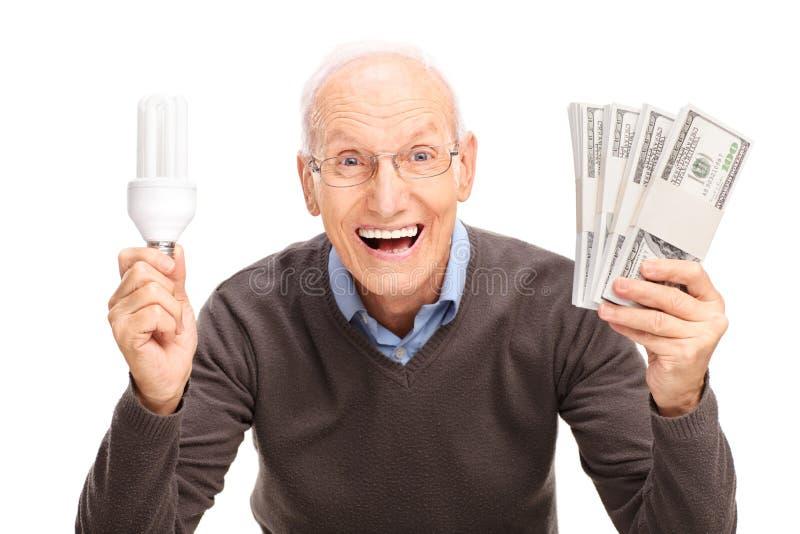 拿着节能电灯泡和金钱的前辈 库存图片