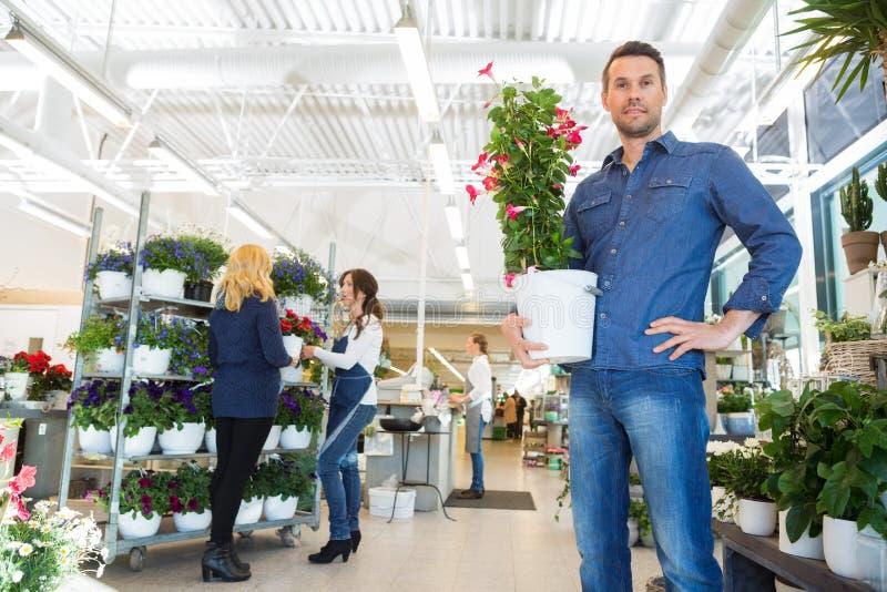 拿着花厂的确信的人在商店 库存照片