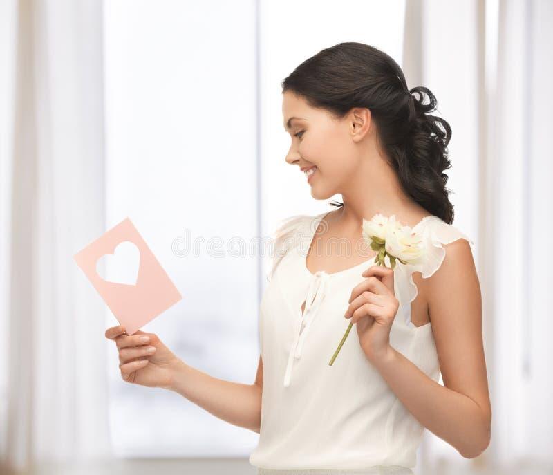 拿着花和明信片的少妇 免版税库存照片