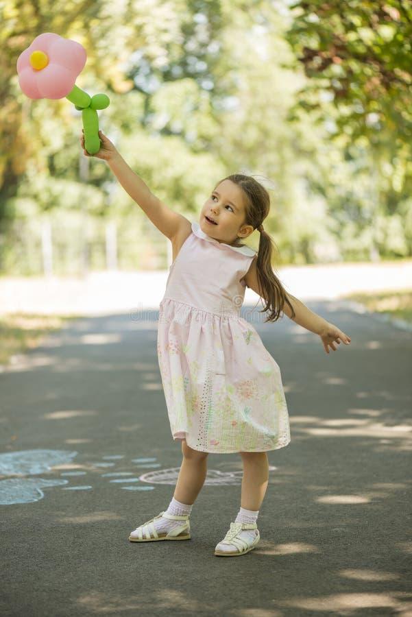 拿着花形状气球的可爱的小女孩户外在夏天公园 免版税库存图片