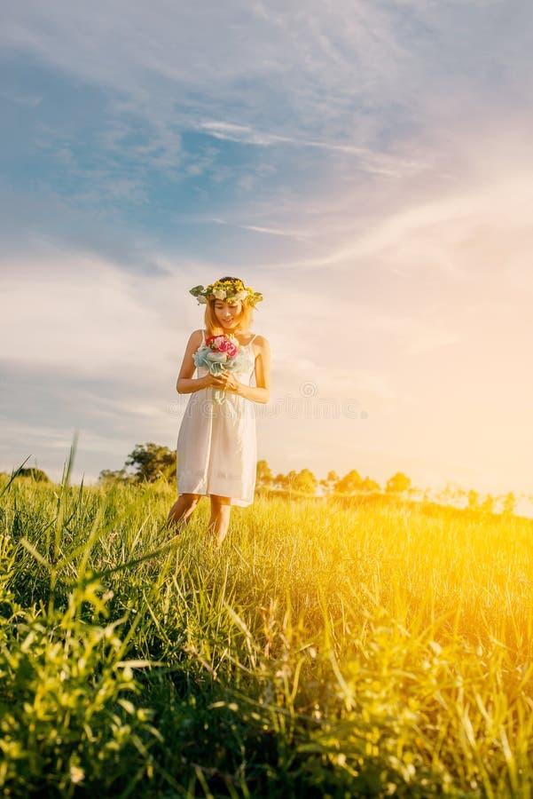 拿着花束桃红色花的年轻美丽的妇女在草甸 免版税库存图片