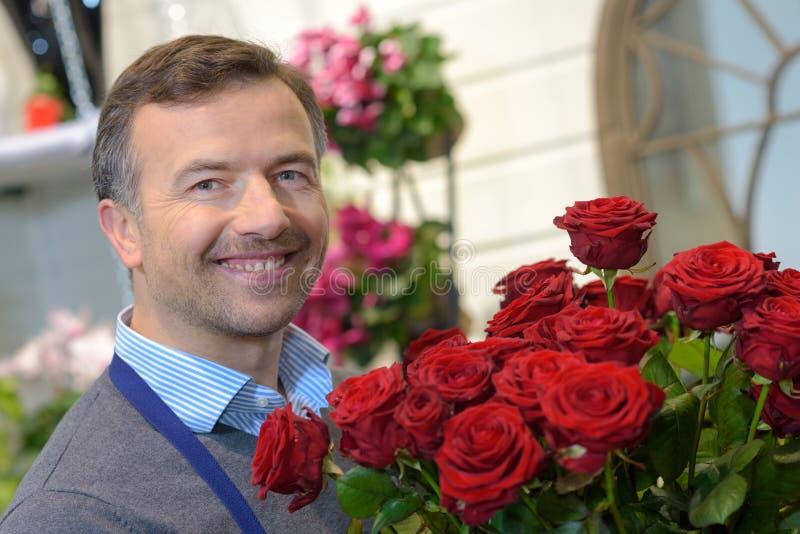 拿着花束玫瑰的人 免版税库存照片