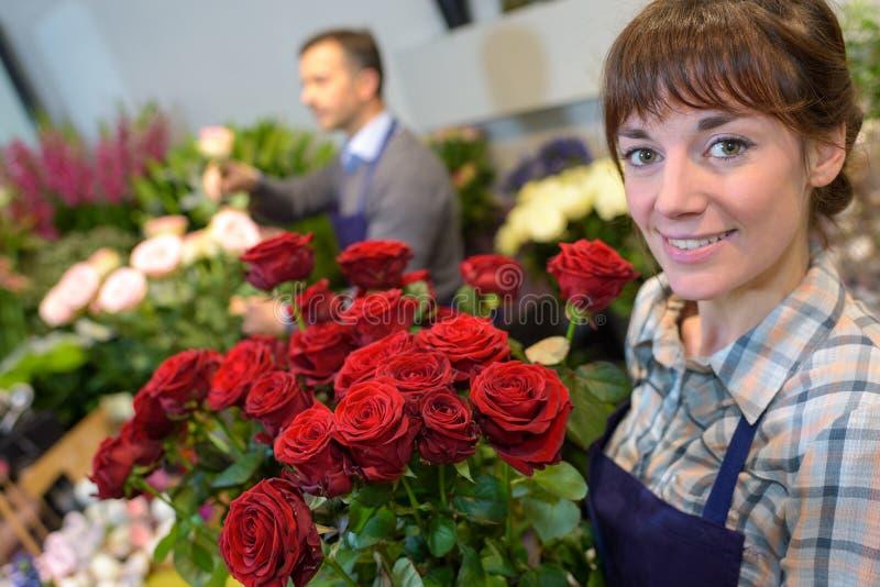 拿着花束玫瑰的卖花人 免版税库存照片