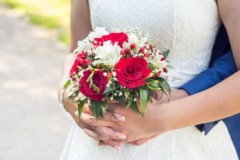 拿着花束的愉快的结婚的婚姻的夫妇照片  免版税图库摄影