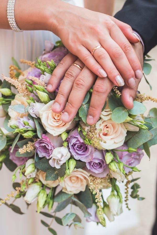 拿着花束的愉快的结婚的婚姻的夫妇照片  图库摄影