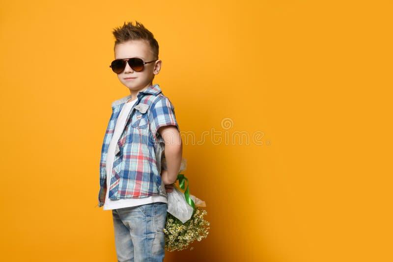拿着花束的逗人喜爱的小男孩 免版税图库摄影