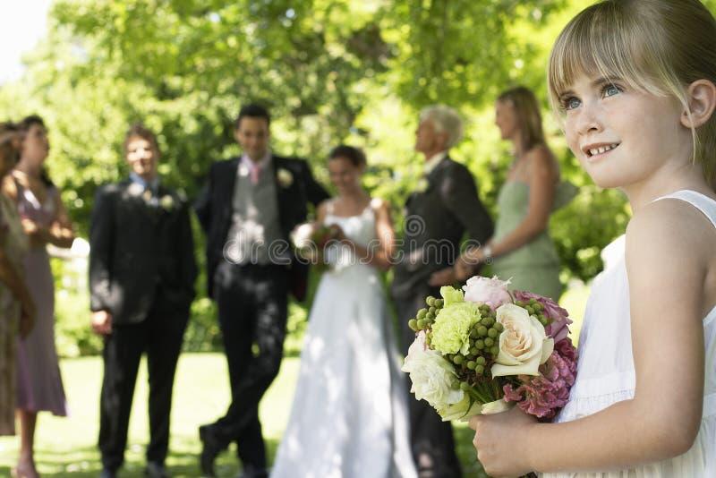 拿着花束的逗人喜爱的矮小的女傧相在草坪 免版税库存图片
