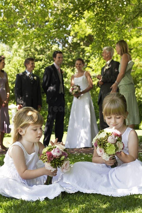 拿着花束的逗人喜爱的矮小的女傧相在草坪 免版税库存照片