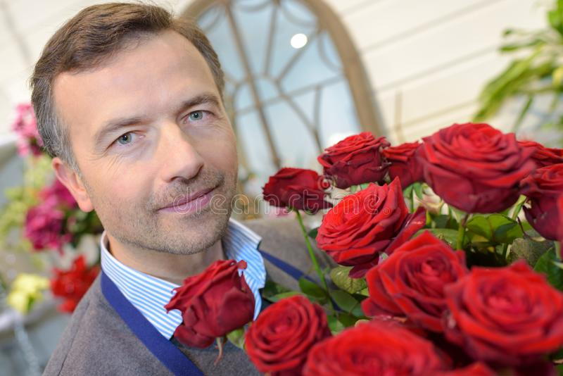 拿着花束美丽的玫瑰的男性卖花人 免版税图库摄影