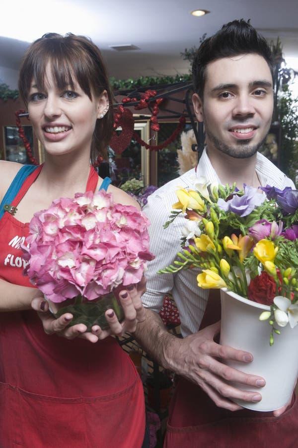 拿着花瓶的确信的卖花人 库存图片