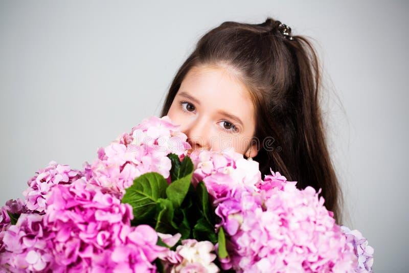 一个拿着花的微笑小女孩的画像 春日可爱的小女孩 带花的甜幼女孩 图库摄影