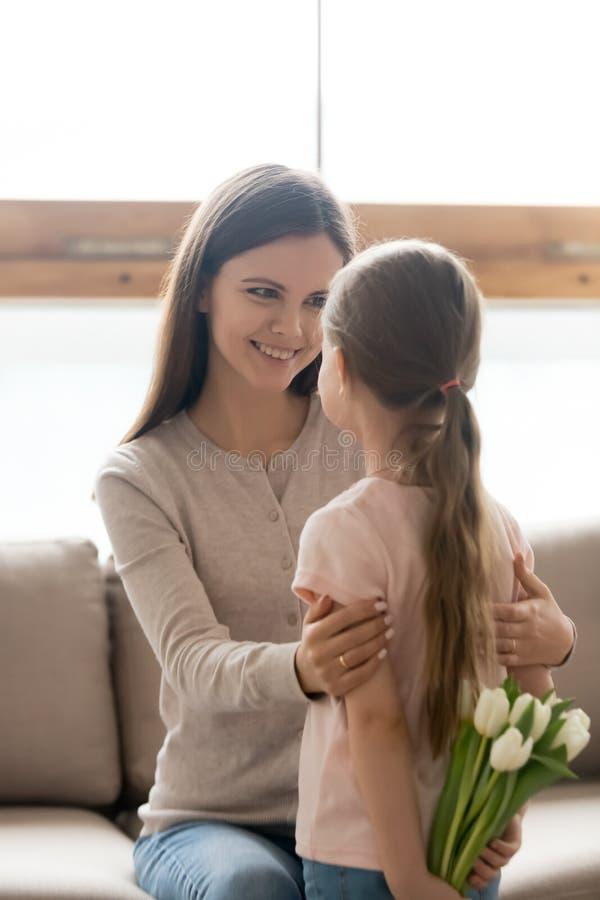 拿着花的可爱的女儿做妈妈的惊奇 库存照片